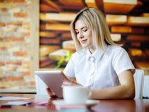 Junge Blondine im Büro, das hinter der Tablette arbeitet Stockfotografie