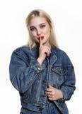 Junge Blondine im Denimjaket und -jeans zeigen Zeigefinger zu den Lippen auf weißem Hintergrund lizenzfreie stockfotografie