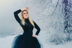 Junge Blondine im schwarzen Kleid im Winter lizenzfreies stockbild