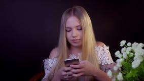 Junge Blondine lächelt auf einem schwarzen Hintergrund Es druckt eine Textnachricht auf dem Smartphone stock video