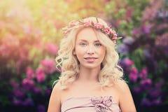 Junge Blondine mit Blumen-Kranz und Sonnenlicht Stockfoto