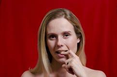 Junge Blondine mit dem Finger in ihrem Mund auf rotem Hintergrund Stockfotos
