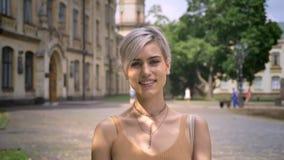 Junge Blondine mit dem kurzen Kamera betrachtenden und lächelnden Haarschnitt, schöne Frau mit durchbohrter Nase stock video footage
