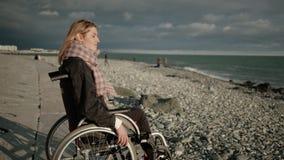 Junge Blondine mit Paralyse von Beinen sitzen im Rollstuhl und sehen Meer an stock footage