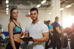 Junge Blondine mit persönlichem Trainer in der Turnhalle stockbilder