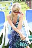 Junge Blondine mit Sonnenbrillen auf einem blauen Stuhl Lizenzfreie Stockfotos