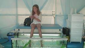 Junge Blondine nimmt Smartphone aus ihrem Geldbeutel heraus, sitzt mit ihren Füßen im Aquarium und erhält Schale von den Fischen stock video
