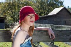 Junge Blondine, Red Hats im Tür-Porträt heraus Lizenzfreie Stockbilder