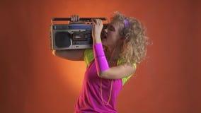 Junge Blondine setzen eine Kassette in das boombox auf ihre Schulter ein stock footage