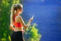 Junge Blondine stehen auf einem blauen Seehintergrund mit einem Handy Eine sportliche Frau benutzt ein Telefon nahe dem Meer Lizenzfreie Stockfotografie