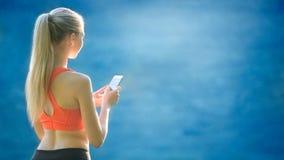 Junge Blondine stehen auf einem blauen Seehintergrund mit einem Handy Eine sportliche Frau benutzt ein Telefon nahe dem Meer Stockfoto