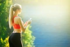 Junge Blondine stehen auf einem blauen Seehintergrund mit einem Handy Eine sportliche Frau benutzt ein Telefon nahe dem Meer Stockfotos
