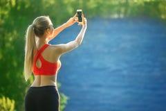 Junge Blondine stehen auf einem blauen Seehintergrund Sportfrau im roten T-Shirt macht selfie auf Natur nahe dem Meer Lizenzfreie Stockfotos