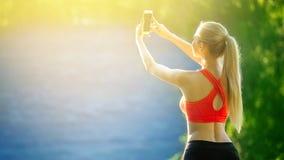 Junge Blondine stehen auf einem blauen Seehintergrund Sportfrau im roten T-Shirt macht selfie auf Natur nahe dem Meer Lizenzfreie Stockbilder