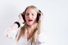 Junge Blondineanhörungsmusik mit Kopfhörern Lizenzfreies Stockfoto