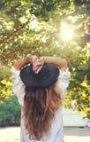 Junge boho Artfrau genießen Sonnenlicht im Sommerpark, Hippie, indie Art, schicker lederner schwarzer Hut, langes Haar, Reisekon stockbilder
