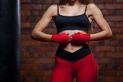 Junge boxende Frauen, die Verpackentasche roter Verband auf Händen Stockfotos