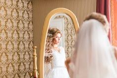 Junge Braut betrachtet im Spiegel Lizenzfreie Stockfotografie