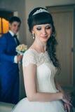 Junge Braut, die auf den Bräutigam im Haus wartet Lizenzfreies Stockfoto