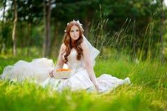 Junge Braut, die auf einem Gras sitzt Stockbilder