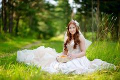 Junge Braut, die auf einem Gras sitzt Stockfoto