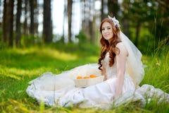 Junge Braut, die auf einem Gras sitzt Stockbild