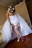 Junge Braut, die das Strumpfband einstellt lizenzfreie stockfotografie