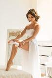 Junge Braut, die Strumpfband auf ihr Bein setzt Stockfoto