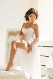 Junge Braut, die Strumpfband auf ihr Bein setzt Lizenzfreie Stockbilder