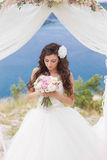 Junge Braut in einem Hochzeitsbogen stockbild