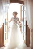 Junge Braut im herrlichen Hochzeitskleid mit umfangreichem Rockblick Lizenzfreie Stockbilder