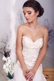 Junge Braut im Hochzeitskleid, das auf Schwingen am Studio sitzt Stockbild
