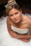 Junge Braut kleidete im weißen Sitzen auf Fußboden an stockbild
