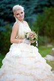 Junge Braut mit einem Blumenstrauß auf der Natur Stockfoto