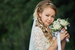 Junge Braut mit einem Blumenstrauß in ihren Händen lizenzfreie stockbilder