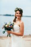Junge Braut mit einem Blumenstrauß von den Blumen, die auf dem Hintergrund den Fluss stehen Lizenzfreies Stockfoto