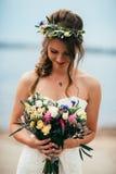 Junge Braut mit einem Blumenstrauß von den Blumen, die auf dem Hintergrund den Fluss stehen Stockfoto