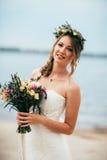 Junge Braut mit einem Blumenstrauß von den Blumen, die auf dem Hintergrund den Fluss stehen Stockfotos