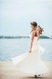 Junge Braut mit einem Blumenstrauß von den Blumen, die auf dem Hintergrund den Fluss stehen Lizenzfreies Stockbild
