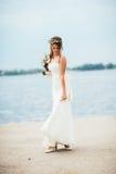 Junge Braut mit einem Blumenstrauß von den Blumen, die auf dem Hintergrund den Fluss stehen Lizenzfreie Stockfotografie