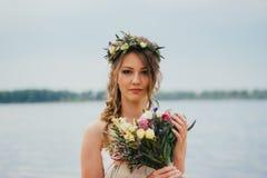 Junge Braut mit einem Blumenstrauß von den Blumen, die auf dem Hintergrund den Fluss stehen Lizenzfreie Stockfotos