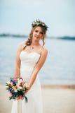 Junge Braut mit einem Blumenstrauß von den Blumen, die auf dem Hintergrund den Fluss stehen Lizenzfreie Stockbilder