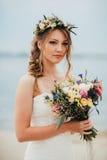 Junge Braut mit einem Blumenstrauß von den Blumen, die auf dem Hintergrund den Fluss stehen Stockbild