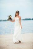Junge Braut mit einem Blumenstrauß von den Blumen, die auf dem Hintergrund den Fluss stehen Stockfotografie