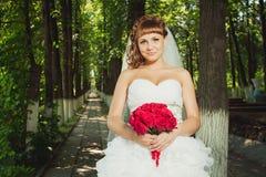 Junge Braut mit rotem Blumenstrauß Stockbild
