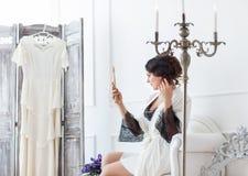 Junge Braut schaut im Spiegel Brautmorgen Lizenzfreie Stockfotos