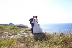 Junge Braut und Bräutigam, die auf die Küste geht Stockbild