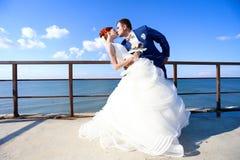 Junge Braut und Bräutigam, die auf die Küste geht Stockbilder