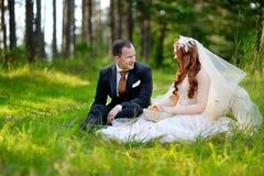 Junge Braut und Bräutigam, die auf einem Gras sitzt Stockfotografie