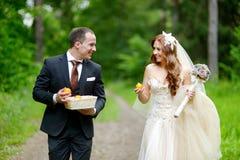 Junge Braut und Bräutigam, die einen Spaziergang macht Stockfotografie